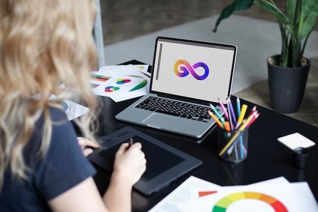 Conceptrice de logo féminin travaillant sur sa tablette connectée à un ordinateur portable