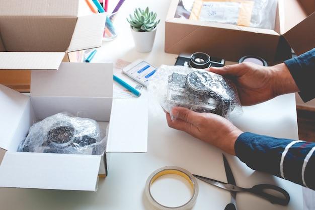 Concepts d'achat en ligne avec un jeune emballant le produit dans la boîte