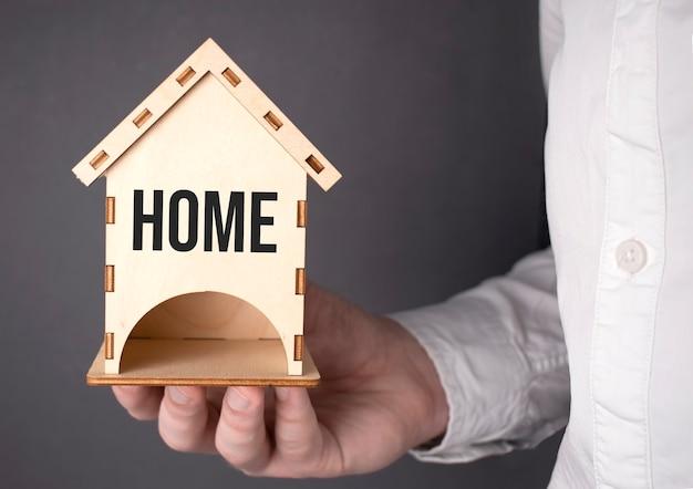 Concepts constructifs. main tenant une maison miniature en bois, la main de l'homme tient symboliquement une mini maison en bois