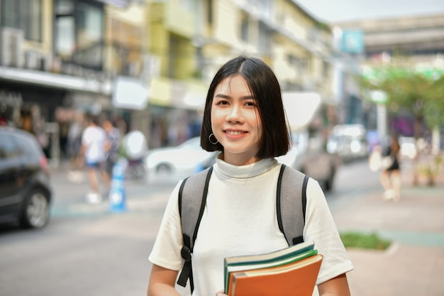 Concepts d'éducation. femmes asiatiques lire des livres dans la ville.