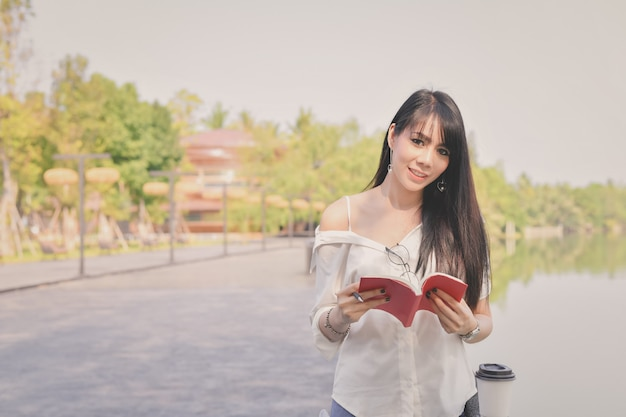 Concepts d'éducation. femmes asiatiques en lisant des livres dans le parc.