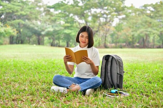 Concepts d'éducation. femmes asiatiques lisant des livres dans le parc.