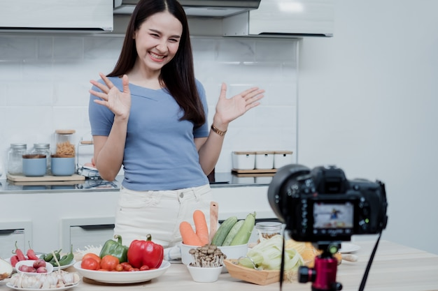 Concepts de médias sociaux une femme heureuse debout dans la cuisine à l'aide d'une caméra et enregistre une vidéo en ligne une vlogger asiatique heureuse a diffusé une vidéo en direct en ligne apprendre à cuisiner dans la cuisine à la maison.