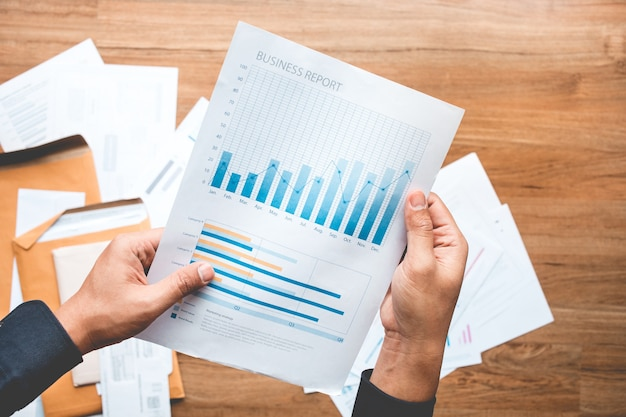 Concepts de réussite commerciale avec homme d'affaires détenant un graphique de rapport papier financier et profit de l'investissement