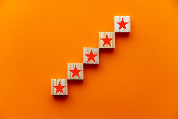 Des concepts tels que l'expérience client, l'enquête de satisfaction, l'évaluation, l'augmentation de la note et la meilleure note des services exceptionnels. le signe cinq étoiles est représenté sur des blocs de bois sur fond orange.