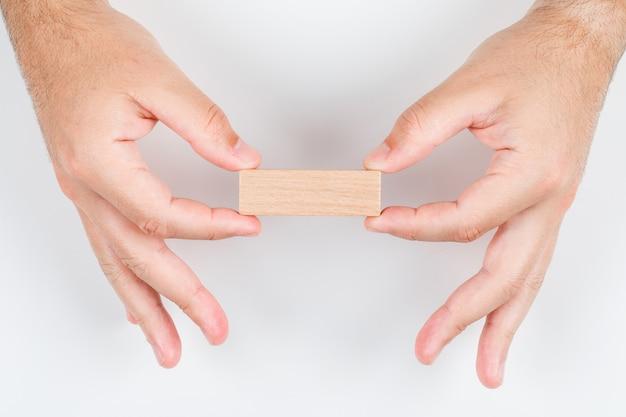 Conceptuel de choix homme tenant une étiquette en bois à deux mains. sur la vue de dessus de fond blanc. image horizontale