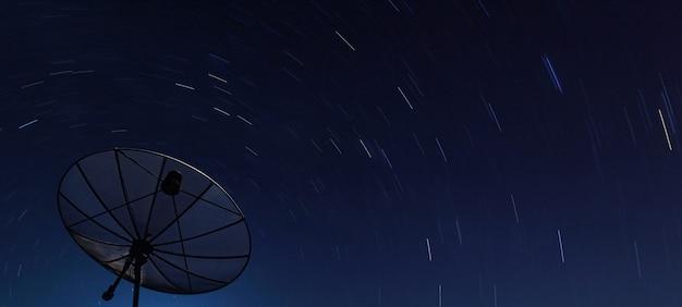 Conceptuel du satellite big black au-dessus d'une étoile à spirale dans la nuit