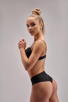 Conceptuel gros plan portrait de fitness athlétique jeune femme en vêtements de sport noir montrant son corps bien formé bodybuilder fit femme confiante isolé sur blanc copie