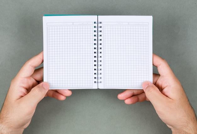 Conceptuel de lecture des notes homme tenant un cahier vide. sur fond gris vue de dessus. espace pour l'image horizontale du texte