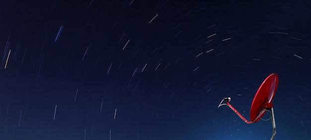 Conceptuel de satellite rouge sur l'étoile en spirale la nuit