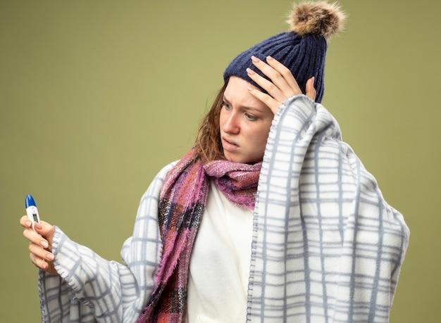 Concerné jeune fille malade portant une robe blanche et un chapeau d'hiver avec écharpe enveloppée dans un plaid tenant et regardant thermomètre isolé sur vert olive