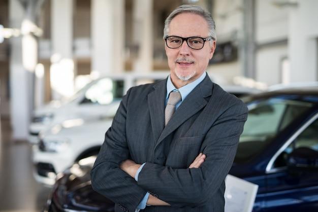 Concessionnaire automobile devant une voiture dans sa salle d'exposition