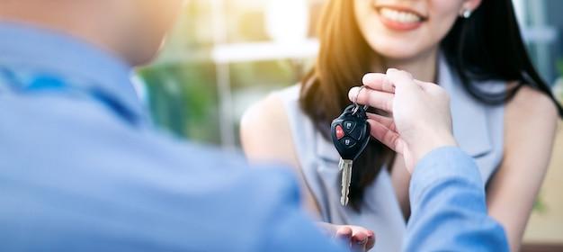 Concessionnaire automobile donnant la clé à distance à une cliente en salle d'exposition