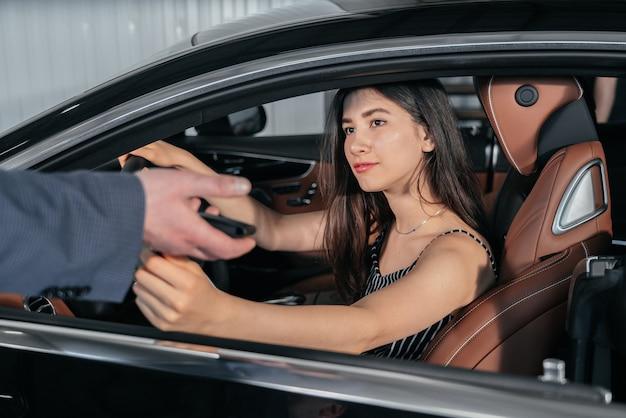 Un concessionnaire automobile donne la clé d'une nouvelle voiture à une jeune femme