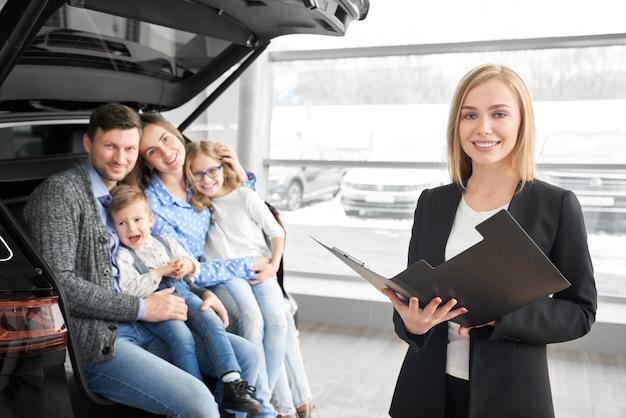 Concessionnaire automobile femme regardant la caméra et posant dans le salon de l'automobile