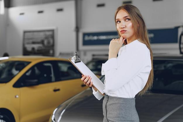 Concessionnaire automobile heureux belle jeune femme dans la salle d'exposition se bouchent