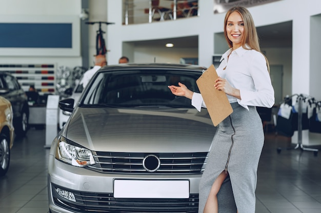 Concessionnaire automobile heureux belle jeune femme dans la salle d'exposition