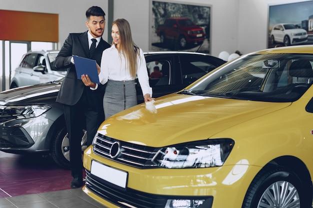 Concessionnaire automobile homme montrant une femme acheteuse une nouvelle voiture dans un salon de voiture