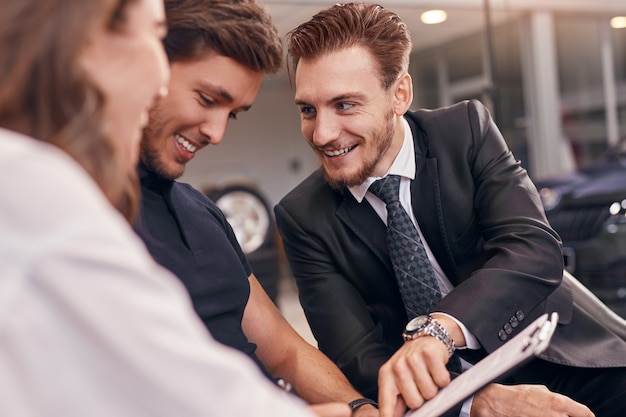Concessionnaire automobile sympathique montrant le contrat aux clients