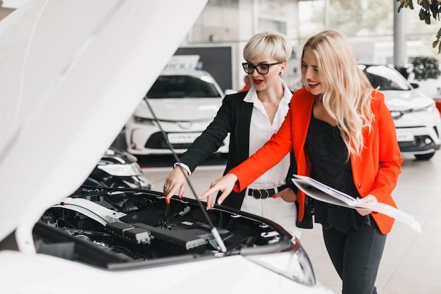 Le concessionnaire avec le client choisit une voiture chez le concessionnaire. regardant à l'intérieur sur le capot de la voiture.