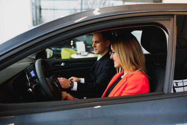 Concessionnaire indien expliquant les caractéristiques de la voiture à un client potentiel