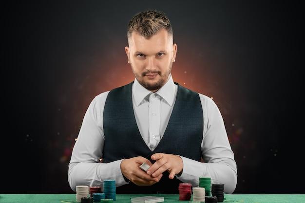Concessionnaire masculin au casino à la table. concept de casino, jeux de hasard, poker, jetons sur la table verte du casino.