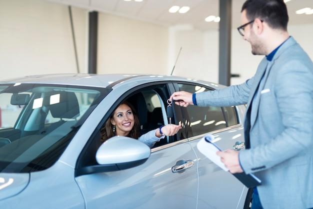 Concessionnaire de véhicules remettant les clés au nouveau propriétaire de la voiture