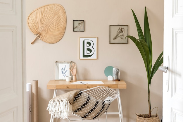 Concevez l'intérieur scandinave de l'espace de bureau à domicile avec de nombreux cadres photo, un bureau en bois, un fauteuil blanc, des plantes, un bureau et des accessoires personnels. home staging neutre et élégant. modèle.