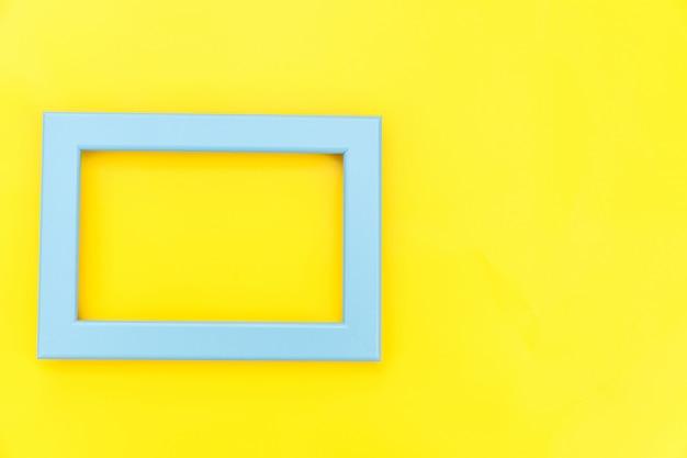 Concevez simplement avec un cadre bleu vide isolé sur fond tendance coloré jaune. vue de dessus, mise à plat, espace de copie, maquette. concept minimal.