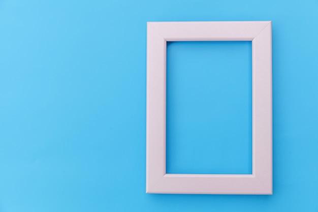 Concevez simplement avec un cadre rose vide isolé sur fond coloré pastel bleu. vue de dessus, mise à plat, espace de copie, maquette. concept minimal.