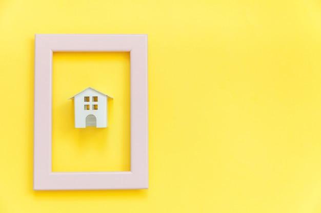 Concevez simplement avec une maison de jouet blanche miniature dans un cadre rose
