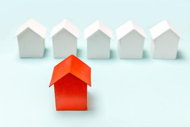 Concevez simplement avec une maison modèle miniature de jouet rouge parmi des maisons blanches isolées sur fond bleu pastel. secteur de l'immobilier. concept communautaire de choix de quartier unique.