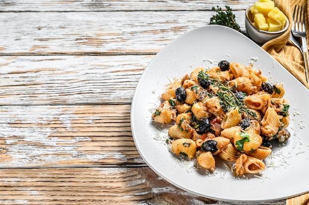 Conchiglie rigate pâtes italiennes à la tomate, olives, câpres, anchois. fond blanc. vue de dessus. copiez l'espace.
