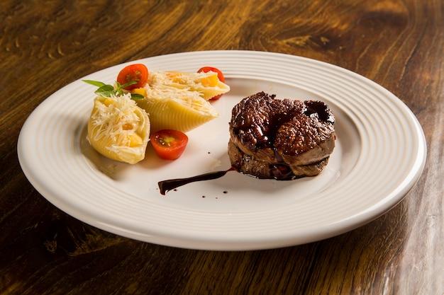 Conchiglioni au four avec fromage cottage et steak de boeuf servi dans l'assiette