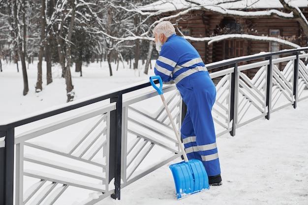 Concierge s'appuyant sur des mains courantes et impatient en hiver