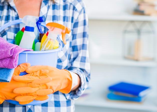 Concierge tenant des équipements de nettoyage dans un seau