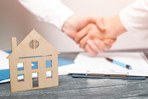 La conclusion du contrat d'acquisition de l'immobilier accompagné d'une poignée de main.