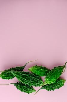 Concombre amer cru ou momordica sur fond vert. légumes asiatiques exotiques. lay à plat, espace de copie