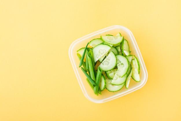Concombre frais tranché et oignons verts dans une boîte sur une table jaune. a emporter, petit déjeuner scolaire. vue de dessus