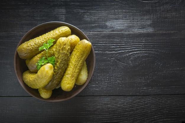 Concombre de légumes en conserve dans un bol sur une planche en bois foncée