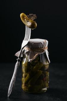 Concombre mariné de cornichons sur un bocal en verre à fourche avec des légumes marinés sur fond noir