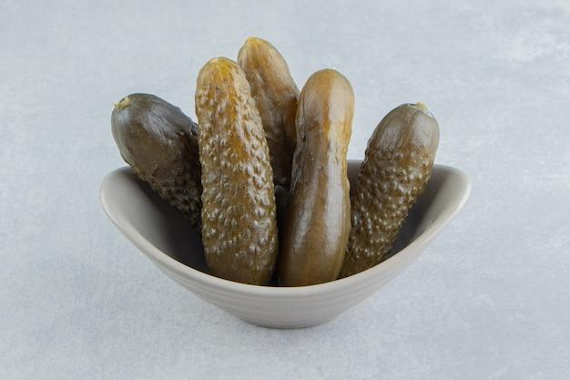 Concombre mariné dans le bol, sur la surface en marbre