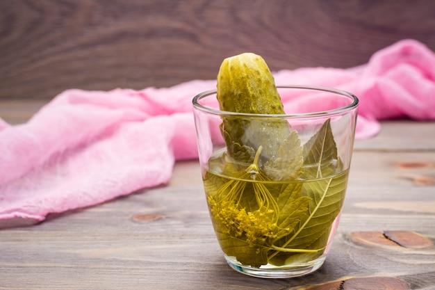 Concombre mariné et marinade dans un verre sur une table en bois