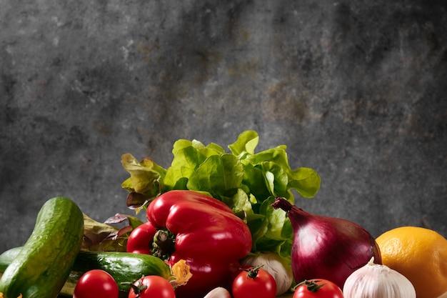 Concombre, tomates, poivrons, ail et laitue sur fond sombre.
