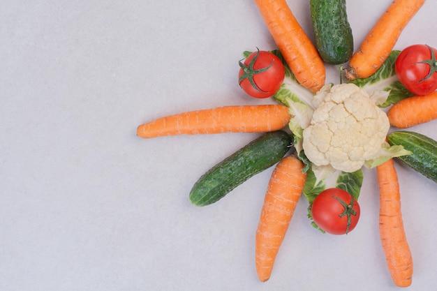 Concombres, carottes, chou-fleur et tomates sur tableau blanc.