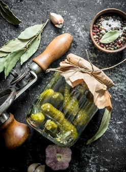 Concombres confits aux épices, feuilles de laurier et ail. sur une surface rustique sombre