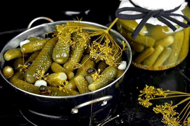 Des concombres en conserve dans une poêle en métal.