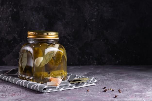 Concombres en conserve fermentés avec feuille de laurier, ail et aneth dans un bocal en verre sur une surface grise