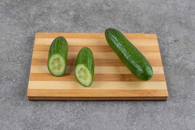 Concombres entiers ou coupés à moitié sur planche de bois sur une surface grise
