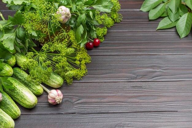 Concombres frais, brins d'aneth et de cerise, ail et baies de cerise. espace de copie. fond en bois. vue de dessus.